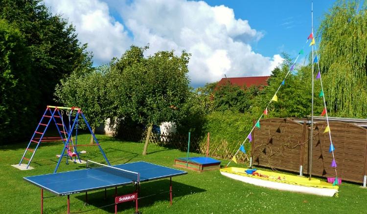 Hof mit Schaukel, Sandkasten und Spielwiese