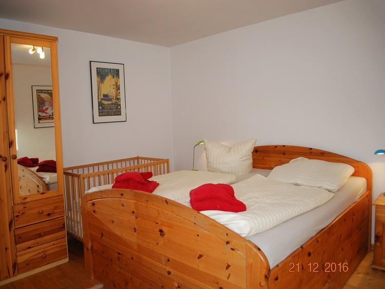 Blick in den unteren Schlafraum mit Doppelbett und Kindergitterbett