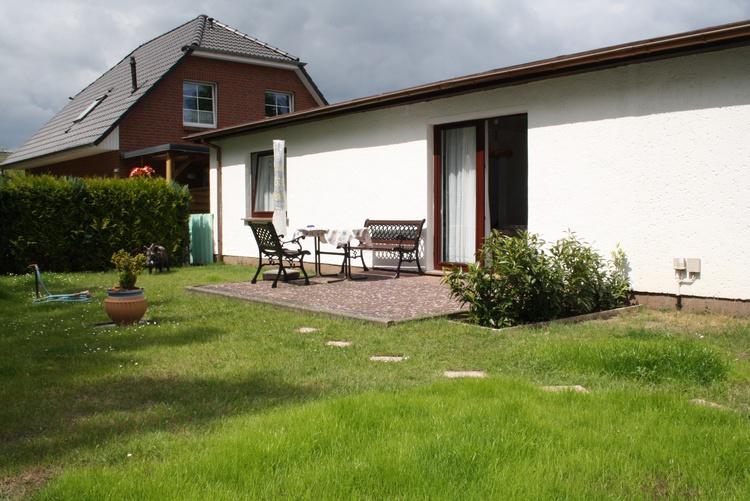 Blick über Garten und Terrasse zur Ferienwohnung