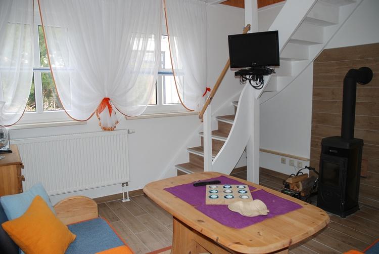 Wohnzimmer mit Kaminofen und Flach TV, Treppe zum Spitzboden
