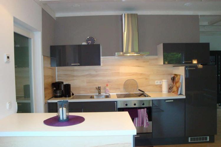 Die offene Küche ist mit Geschirrspüler und Herd mit Ceranfeld ausgestattet