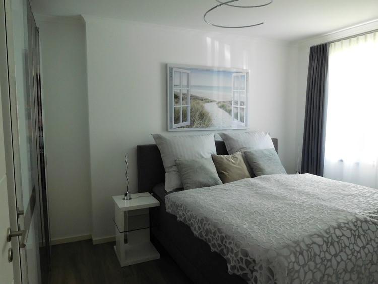 Schlafzimmer mit Boxspringbett und großem, verspiegeltem Schrank