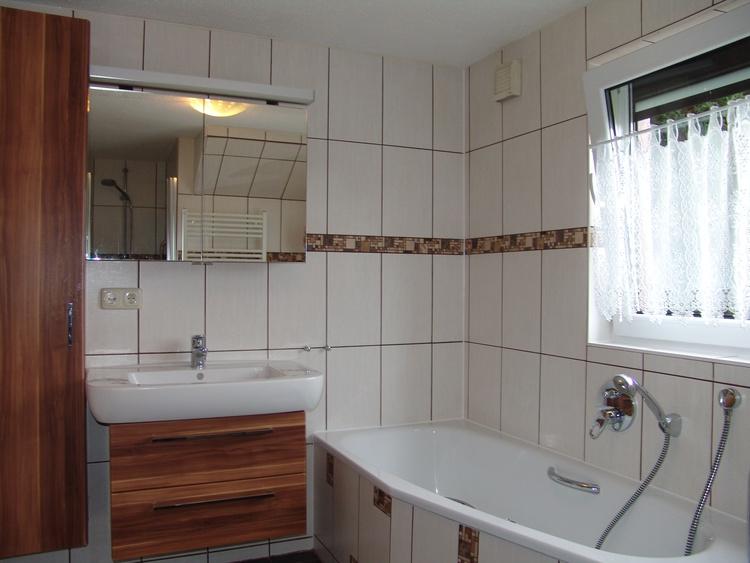 Im modernen Badezimmer befindet sich auch eine Wanne für ein entspannendes Wohlfühlbad.