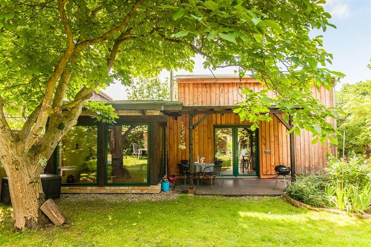 Die überdachte Veranda und der Wintergarten vom Garten aus gesehen