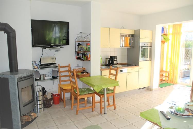 Wohnzimmer mit Einbauküche, Kaminofen