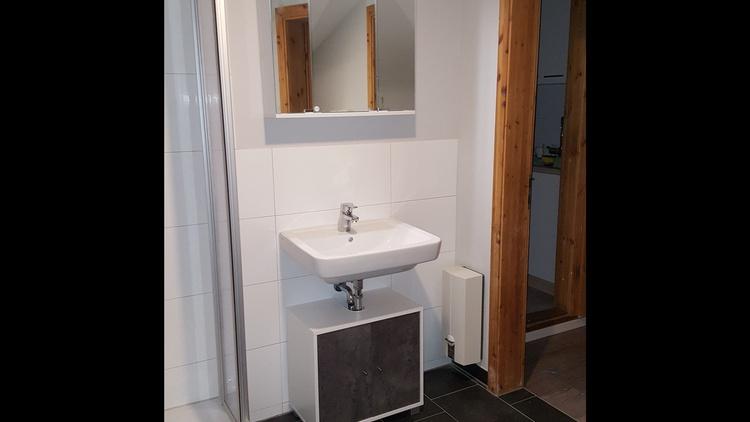 Badezimmer mit Dusche, WC, Fön und Schminkspiegel